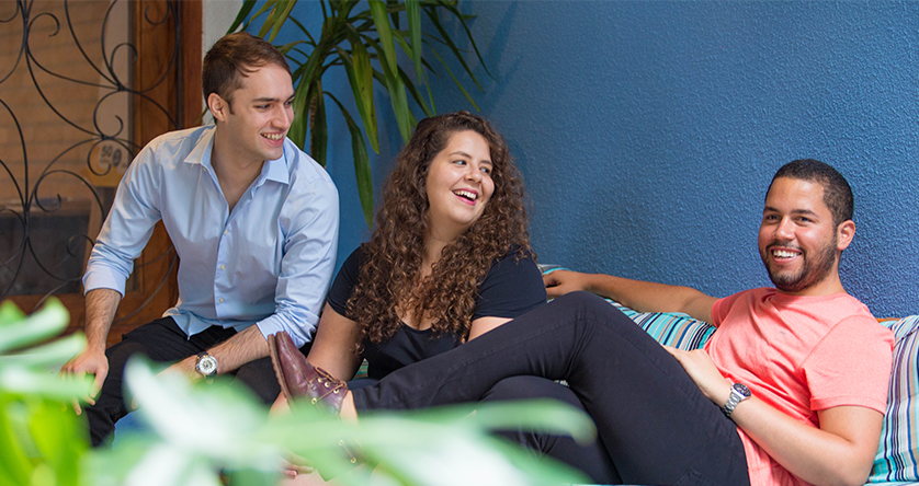 Cuidas founders João, Deborah, and Matheus (now an active board member) sit together on a couch.