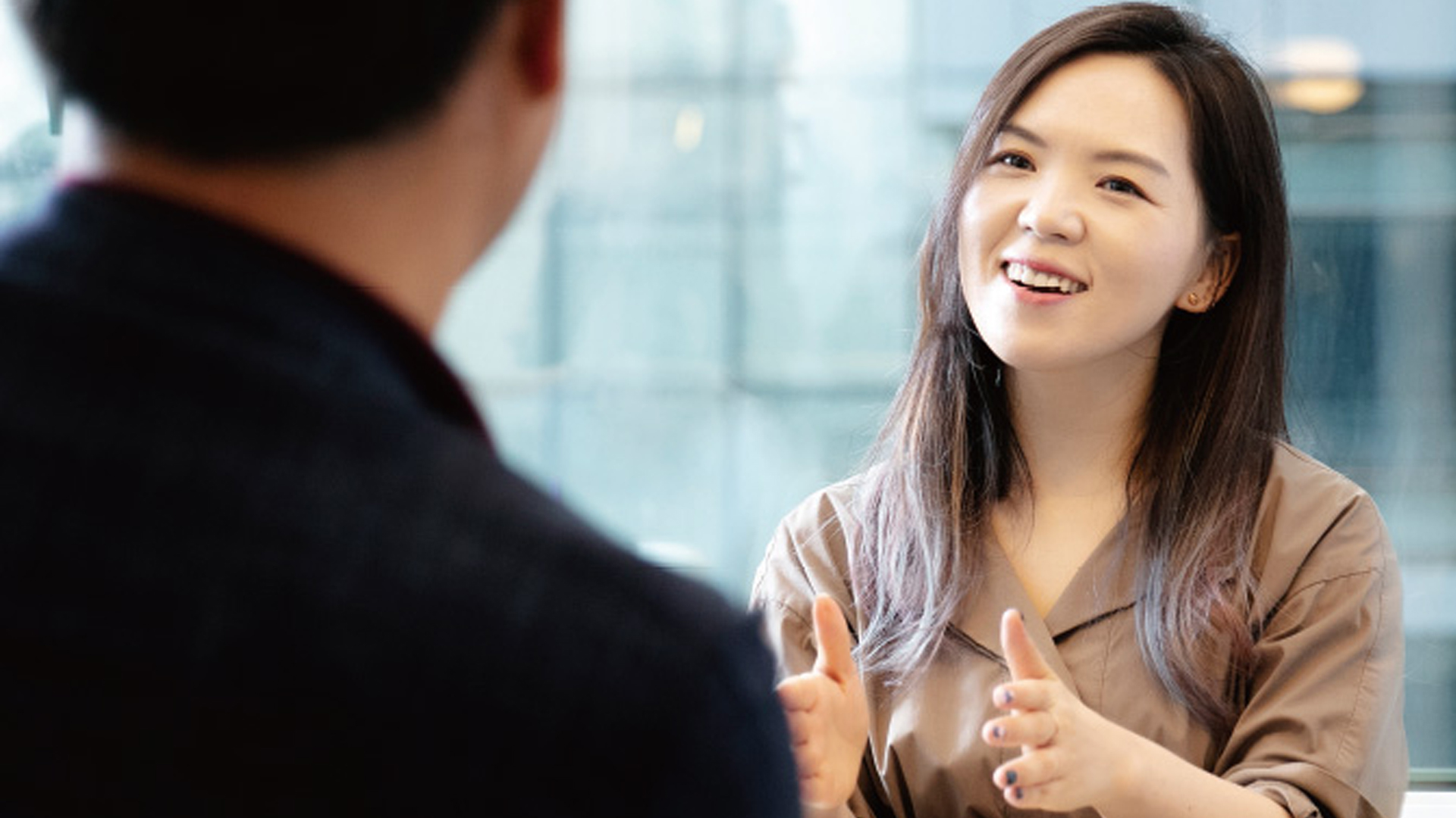 Hanna Kim of Grip smiling while talking to a man