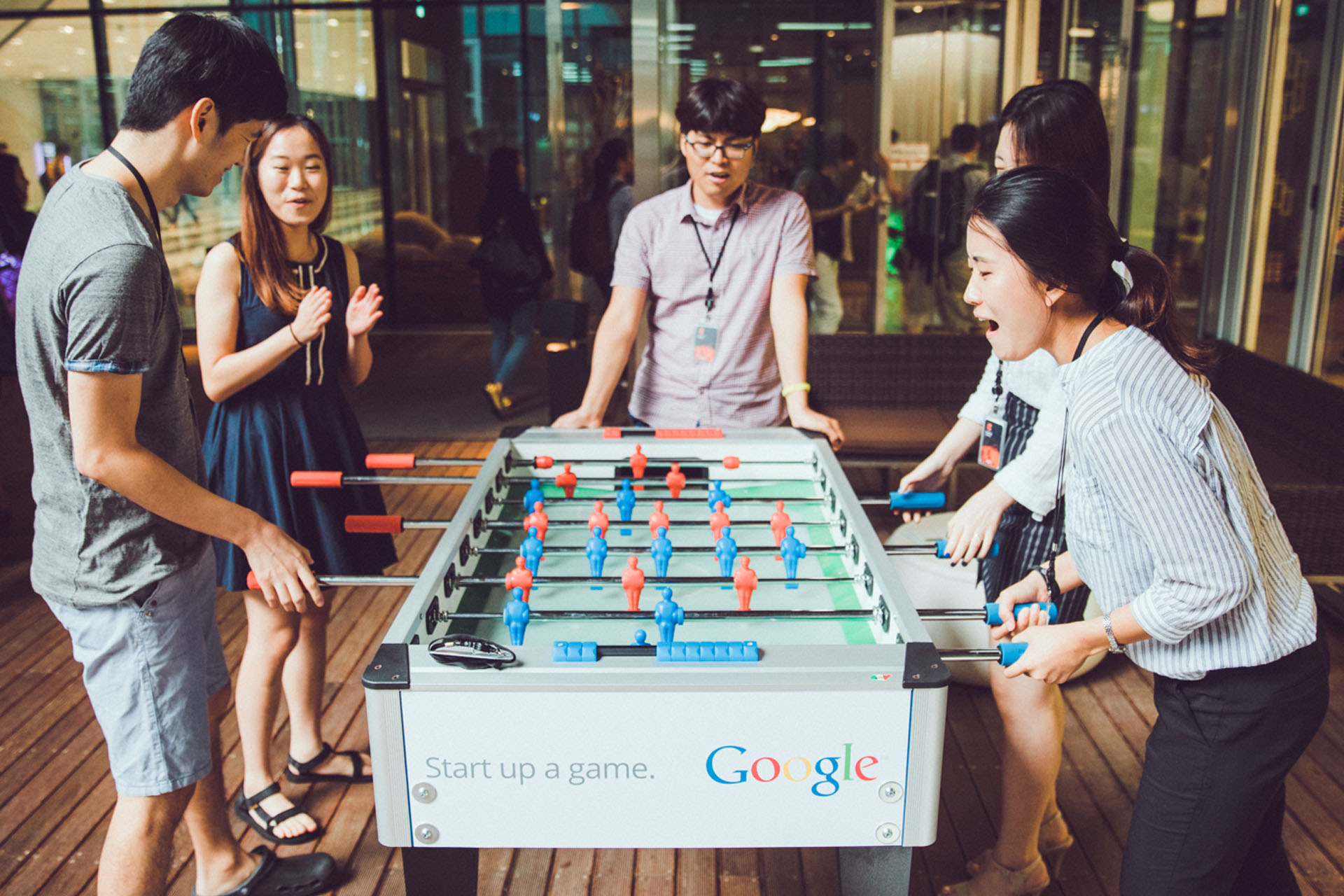 A group of colleagues playing foosball